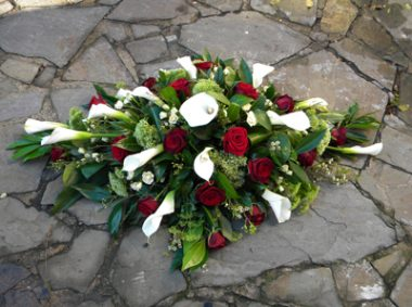 Red roses and cala lilies funeral spray